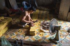 Dong Anh, Hanoi, Vietnam - 20 Sep, 2015: De Aziatische mannelijke arbeider maakt houtsnijwerk in zeer kleine en smalle workshop i Stock Foto