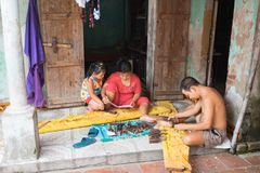 Dong Anh, Hanoi, Vietnam - Sep 20, 2015: A man and his wife make wood carving products in front of their house in Dao Thuc village.  Royalty Free Stock Images