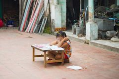 Dong Anh, Hanoi, Vietnam - Sep 20, 2015: Schoolgirl do homework  on table on yard in front of her house. Lacking of good education. Condition is a problem of Royalty Free Stock Images