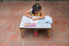 Dong Anh, Hanoi, Vietnam - Sep 20, 2015: Schoolgirl do homework  on table on yard in front of her house. Lacking of good education. Condition is a problem of Stock Photo