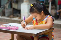 Dong Anh, Hanoi, Vietnam - Sep 20, 2015: Schoolgirl do homework  on table on yard in front of her house. Lacking of good education. Condition is a problem of Royalty Free Stock Photo