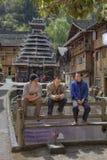 Dong-Minderheitsdorf, drei Chinesen stehen auf Bank, Guizhou, Chi still Stockbild