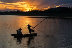 Dong Mo lake with a couple of fishers catching fish by net trap in beautiful sunset period in Son Tay town, Hanoi, Vietnam.  Royalty Free Stock Image