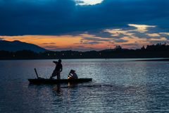 Dong Mo lake with a couple of fishers catching fish by net trap in beautiful sunset period in Son Tay town, Hanoi, Vietnam.  Stock Photo