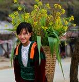 DONG VAN HA GIANG, VIETNAM, Januari 01, 2017: Oidentifierade ungar för etnisk minoritet med korgar av rapsfröt blommar i Hagiang Royaltyfria Bilder