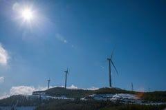 Dongchuan, tierra roja de Yunnan que juega Macan después del grupo de la turbina de viento de la nieve Foto de archivo