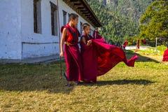Милый молодой монах послушника позволил его робе порхая в ветре, восточном Бутане стоковая фотография rf