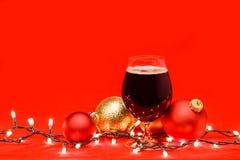 Donker aalbier in een tulpenglas met Kerstmissnuisterijen en lichten royalty-vrije stock afbeeldingen