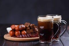 Donker bier en smakelijke geplaatst biersnacks Twee mokken stout, streven na royalty-vrije stock afbeelding