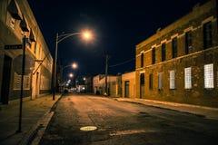 Donker en eng stedelijk industrieel stadsdistrict bij nacht stock foto's