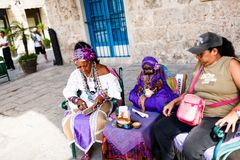 Donker-gevilde Cubaan in wit kostuum vertelt fortuinen aan toeristen in de straten van Havana stock foto's