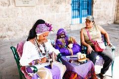 Donker-gevilde Cubaan in wit kostuum vertelt fortuinen aan toeristen in de straten van Havana royalty-vrije stock fotografie