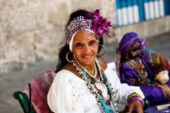 Donker-gevilde Cubaan in wit kostuum vertelt fortuinen aan toeristen in de straten van Havana royalty-vrije stock foto