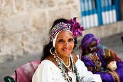 Donker-gevilde Cubaan in wit kostuum vertelt fortuinen aan toeristen in de straten van Havana stock foto