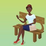 Donker-gevilde vrouwenzitting op een bank Stock Foto