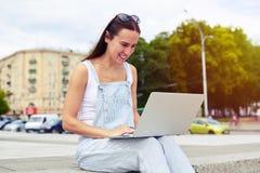 Donker-haired aantrekkelijke vrouw die in overall terwijl het werken glimlachen Stock Afbeeldingen