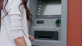 Donker-haired jonge vrouw voor ATM Stock Foto's