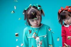 Donker-haired ongebruikelijke meisjes met gezichtseigenschappen die terwijl confettien het vallen bevinden zich stock foto's
