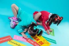 Donker-haired tweelingzusters in het kleurrijke kleding omringd zitten royalty-vrije stock foto