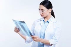 Donker-haired vrouwelijke arts die de resultaten van het Röntgenstraalonderzoek bestuderen stock foto's
