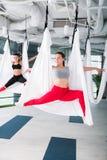 Donker-haired yogatrainer die haar cliënten luchtyoga onderwijzen stock fotografie