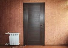Donker houten gesloten deurclose-up op de muur met rood uitstekend behang en witte batterijradiator Stock Fotografie