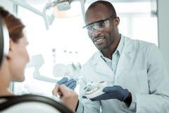 Donker-huid Afrikaanse Amerikaanse tandarts die gewone benoeming hebben stock afbeeldingen