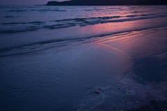 Donker overzees zandig strand en rode de schemeringoceaan van de zonlichtzonsondergang stock fotografie