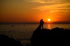 Donker silhouet op zonsondergang dichtbij oceaan Stock Afbeeldingen
