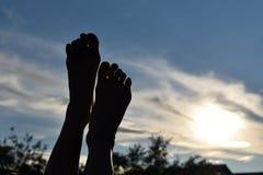 Donker silhouet van benen bij zonsondergang in hemel Voeten benen aan de zon worden opgeheven die stock afbeelding