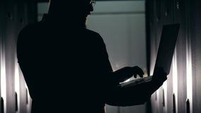 Donker silhouet van een mens die op laptop typen stock videobeelden