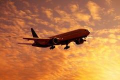 Donker silhouet van vliegtuigen tegen een oranje hemel stock foto's