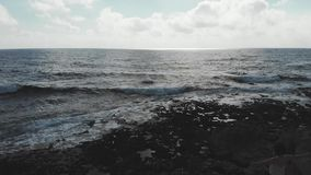 Donker silhouet van vrouwelijke persoon met wapens brede open in lucht die zich op klip met sterke golven bevinden die oceaanstra stock videobeelden