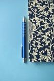 Donkerblauw en wit bloemennotitieboekje met blauwe potloden op witte en blauwe achtergrond, detail Stock Afbeeldingen
