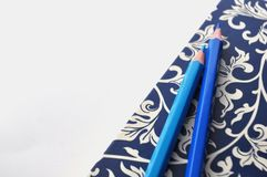 Donkerblauw en wit bloemennotitieboekje met blauwe potloden op witte en blauwe achtergrond, detail Royalty-vrije Stock Afbeeldingen
