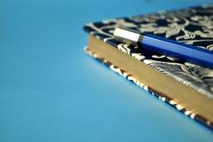 Donkerblauw en wit bloemennotitieboekje met blauwe potloden op witte en blauwe achtergrond, detail Stock Foto