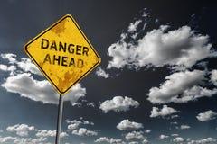 Donkerblauwe bewolkte hemel en gele langzaam verdwenen verkeersteken Stock Afbeeldingen