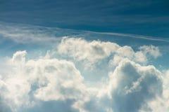 Donkerblauwe de zomerhemel met pluizige wolken Stock Afbeeldingen
