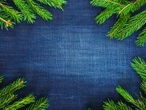 Donkerblauwe denimachtergrond, sjofel, oud in de midden en groene nette takken Royalty-vrije Stock Afbeeldingen