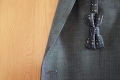 Donkerblauwe gevormde vlinderdas op de grijze achtergrond van het kostuumjasje Stock Fotografie