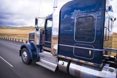 Donkerblauwe glanzende klassieke grote installatie semi vrachtwagen die op de weg w lopen Royalty-vrije Stock Fotografie