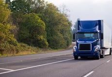 Donkerblauwe grote de installatie semi vrachtwagen van de dagcabine met semi aanhangwagen die o in werking stellen Royalty-vrije Stock Foto