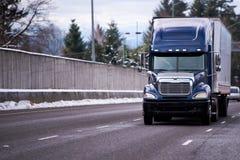 Donkerblauwe grote installatie semi vrachtwagen met het droge vervoer van de bestelwagen semi aanhangwagen royalty-vrije stock foto