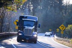 Donkerblauwe grote installatie semi vrachtwagen op zonnige windende weg Stock Foto