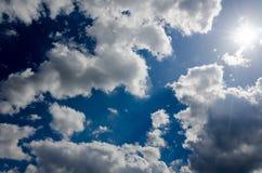 Donkerblauwe hemel met wolken en zon royalty-vrije stock foto