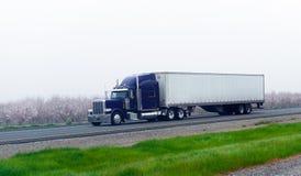 Donkerblauwe klassieke semi vrachtwagen met chroom droge van trailer op bloo Royalty-vrije Stock Afbeelding