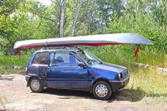 Donkerblauwe kleine die auto, met kajak wordt geladen Royalty-vrije Stock Afbeeldingen