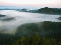 Donkerblauwe mist in diepe vallei na regenachtige nacht Rotsachtig de meningspunt van de heuvelblaasbalg De mist beweegt zich tus Stock Foto