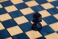 Donkerblauwe ridder op houten schaakbord Stock Afbeelding
