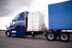 Donkerblauwe semi vrachtwagen met opslagcontainer en aanhangwagen Royalty-vrije Stock Foto's